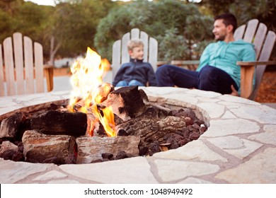 view of firepit and happy smiling family of two, father and son, enjoying time together in the background