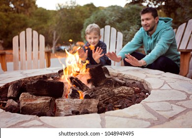 view of firepit and happy smiling family of two, father and son, warming their hands by the fire and enjoying time together in the background