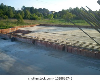 A view of the first floor of a house under construction, wooden formwork, screed, rebar, red bricks, walls