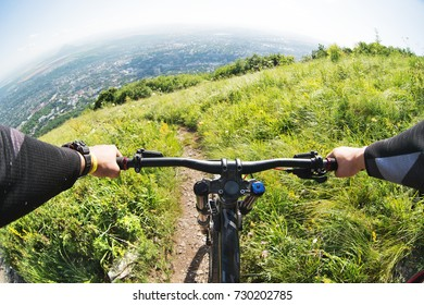 View from the first person of a cyclist riding downhill from a high mountain in the background of a city in the distance