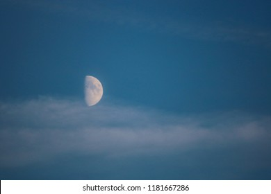 View of first quarter of moon in a blue light sky