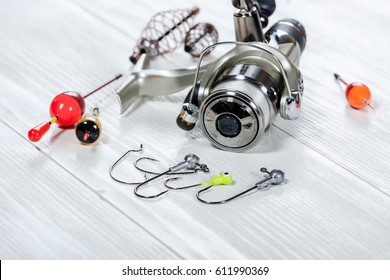 View of fishing accessories on white wooden table. Items include fishing reel, hooks, floats and dock.