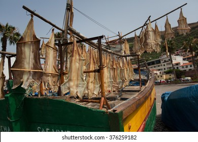 View of fishing boat and dry fish hanging in Camara de Lobos town in south of Madeira island, Portugal
