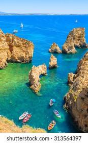 View of fishing boats on sea at Ponta da Piedade rocky coast, Algarve region, Portugal