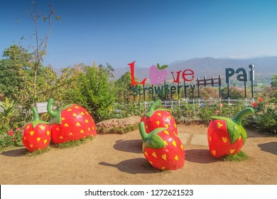 view of five big red Strawberry models in the garden with text Love Pai Strawberry and blue sky background, strawberry farm at Pai District, Mae Hong Son, Thailand.