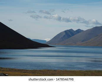 View up fjord in the Western Fjords region of Iceland - calm water, blue with mountains either side