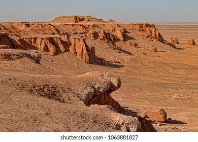 View of Flaming Cliffs in Mongolian Gobi Desert. Natural Rock Formations over Flat Desert Plains.