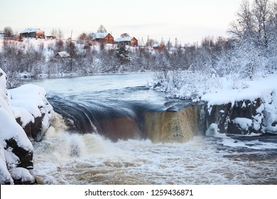 View of a flat waterfall with village on the hill. Sunset at winter season. District of the village Nadvoitsy, Segezha, Karelia republic, Russia