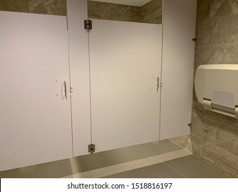 View of floating bathroom stall in public restrooms. Ceiling suspended stalls.