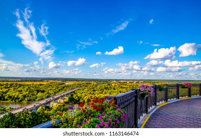View from floral balcony at mountain valley town panorama. Balcony flowers panoramic view. View from balcony flowers panorama