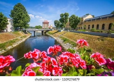 View of flowers on the bridge and pedestrian bridge across river Vuka in Vukovar, Croatia.