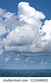 View of fluffy white clouds floating slowly above blue water of sea in sunlight, Cuba