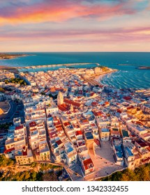 View from flying drone. Fantastic morning cityscape of Vieste - coastal town in Gargano National Park, Italy, Europe. Coloful spring sunrise on Adriatic sea. Traveling concept background.