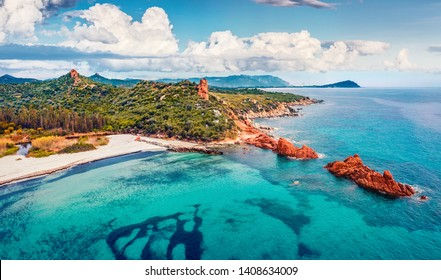 View from flying drone. Wonderful summer view of di Cea beach with Red Rocks Gli Scogli Rossi - Faraglioni. Aerial morning scene of Sardinia island, Italy, Europe. Beauty of nature concept background.