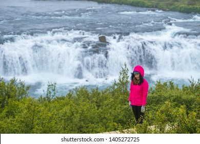 View fo asian woman traval of faxi waterfall in Iceland, The Faxi (or Vatnsleysufoss) waterfall is located on the Golden Circle, a popular tourist trail east of Reykjavik. The waterfall is located on