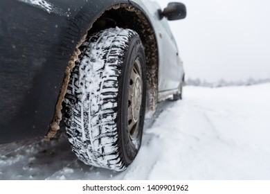 View focused on the car tire and  bumper  on winter road covered with snow. Vehicle on snowy road after snowfall.