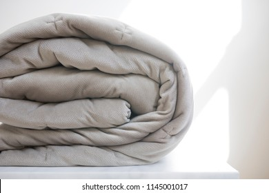 View of a folded beige natural quilt doona cover on a white marble table against a bright white background with light cast by a near by window