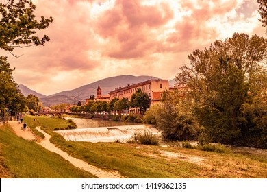 A view of Foligno, crossed by the river Topino, a bell tower rises above the roofs of the houses. The cloudy sky at sunset. The canal, the bridge, the trees. Some people walk in the park with the dog.