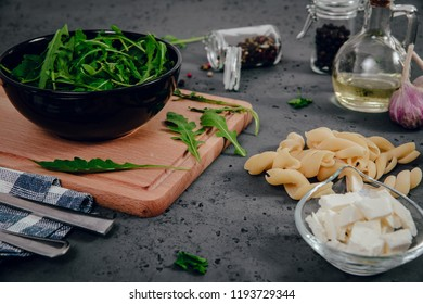 A view of food ingredients, rucola, garlic, dried tomatoes in brine, pasta, feta cheese. The concept of preparing dishes with pasta and rucola on a stone counter top. Food photography.