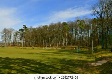 View of a football field or pitch with goalpost and lighting elements located next to a dense forest or moor seen on a cloudy yet warm spring day on a Polish countryside