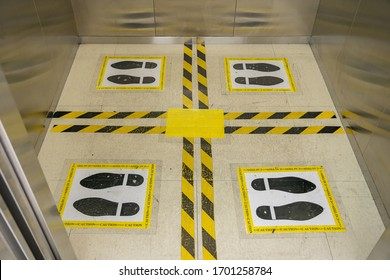 View of footprint sign for stand in lift. Social distancing with COVID-19 coronavirus crisis. yellow footprint sign with text caution social distance, Social distancing the elevator (Lift) in hotel.