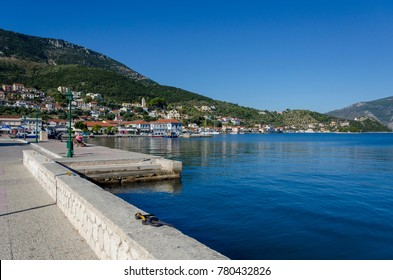 View in the foreground the pier then the port with its fishing boats moored the port facilities and finally the mountains that surround the port of vathy on the Ionian island of Ithaca