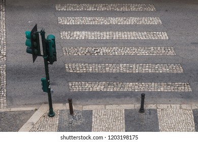 View form above on the crosswalk and a traffic light. Lines of the crosswalk paved by cobblestones the same as the footpath. Lagos, Algarve, Portugal.
