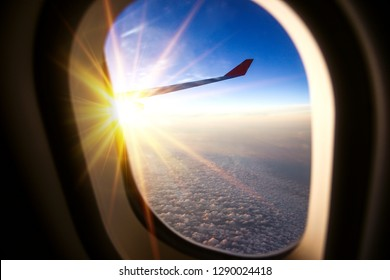View form airplane window with the child look outside on sunrise with cloud.