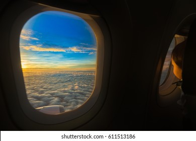View form airplane window with the child look outside on sunset with cloud.