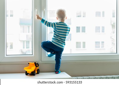 View form behind of toddler child standing in front of a big window leaning against it looking outside, waiting for something