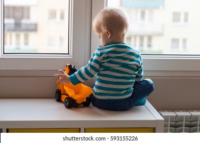 View form behind of toddler child sitting in front of a big window leaning against it looking outside, waiting for something