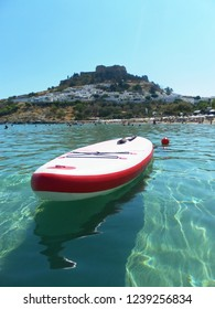 View of the fortress in Lindos. The Island Of Rhodes. Greece.  Surfboard on the water.