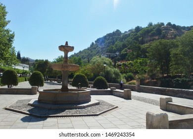 View of a fountain at Carrera del Darro with Generalife gardens in the background. Granada, Andalusia, Spain