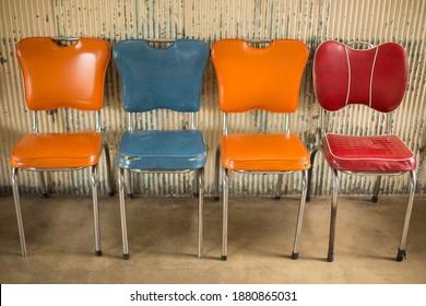 Vue sur quatre beaux fauteuils de table recouverts de vinyle vieux et vieux avec cadres métalliques
