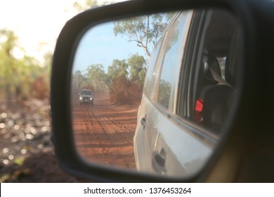 View of four wheel drive vehicle driving behind in the rear mirror along a red, corrugated, dusty road in Australia's top end Kimberley, Western Australia.