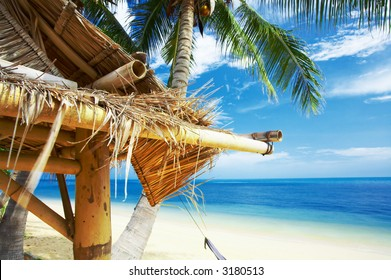 view of a fragment of nice exotic bamboo hut on tropical beach