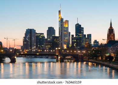 View of Frankfurt am Main skyline at dusk along Main river with cruise ship in Frankfurt, Germany