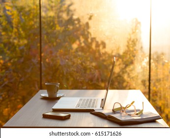 View of Freelancer working Place at wooden Table with Computer Coffee Mug Notepad Telephone and Glasses at Morning in Forest Villa