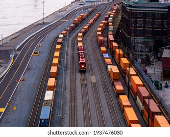 view of a freight train with a red locomotive in between two other freight trains