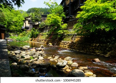 View of fresh river stream, stone bank and natural rock beach with green trees and local buildings in Kurokawa onsen town, Japan