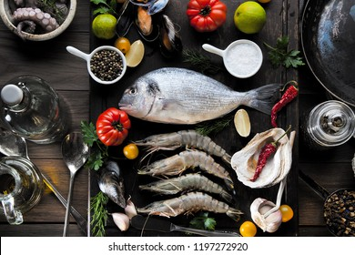 up view of fresh sea food on grunge textured black background. Shrimps, bream, herbs, lemon