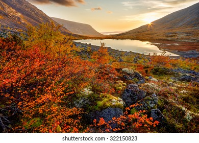 View of freshwater lake Tahtarjavr in Malaya Belaya valley in Hibiny mountains with colorful autumn tundra in foreground and sunset rays in background