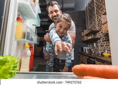view from fridge on father holding daughter while she trying to reach for food