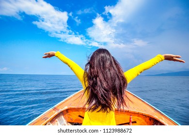 View from the front Asian woman sitting on front or thai wooden long tail boat and raise up her hand when going to the  island against nice clear blue sky in the sea, Beautiful Nature Place Thailand.