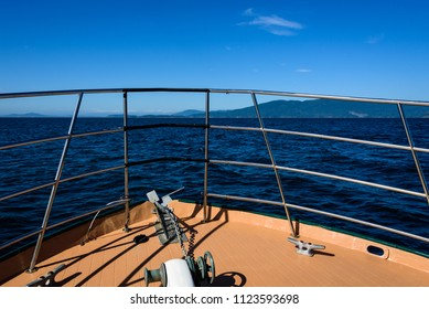 View of the front of a boat, deck, anchor and railings, cruising on the Salish Sea to the San Juan Islands, blue water and sky