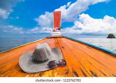 """View from the front or head of Thai wooden long tail boat set with tourist hat have wording """"Thailand"""" and sun glass against clouds of storm sky in lipe island sea, Beautiful Nature Place in Thailand."""