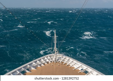 View from front at the rough seas and waves forward of bow of cruise ship