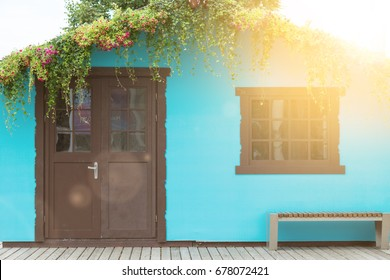 View from the front of the wooden brown door on the blue house with a window