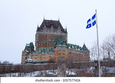 View of Frontenac Castel (Chateau de Frontenac, in French) in winter under the snow with a Quebec flag waiving. The Chateau Frontenac is a grand hotel in Quebec City