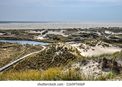 View froon the German Northsea island of Amrumm the top of a hig dune towards the Northsea across a landscape with dunes, ponds and a long plankbridge on the German Northsea island of Amrum